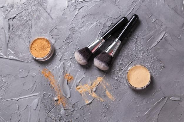 Mineraal poeder van verschillende kleuren met borstels voor make-up op houten bovenaanzicht als achtergrond