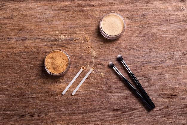 Minerale poederstichting met borstels op een houten ondergrond. milieuvriendelijke en biologische schoonheidsproducten