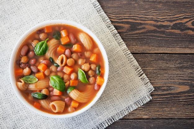 Minestrone groentesoep met pasta in een witte kop op een linnen servet bovenaanzicht