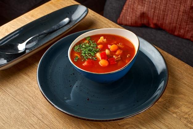 Minestrone, italiaanse groentesoep met pasta op een houten tafel.