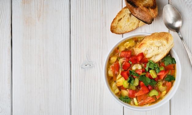 Minestrone soep in witte schotel op witte houten tafel