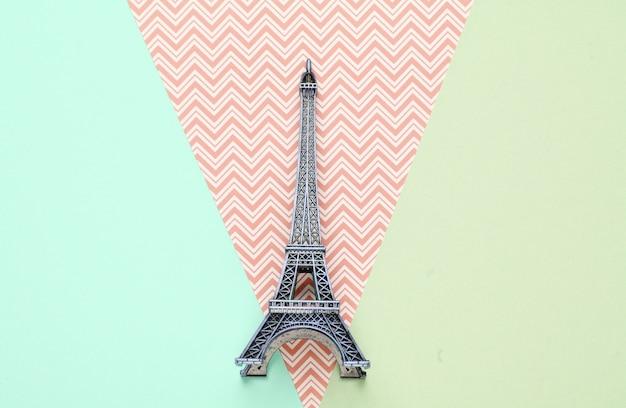 Mini beeldje van de eiffeltoren op een pastel papier achtergrond. bovenaanzicht