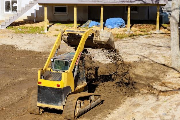 Mini bulldozer landschapsarchitectuur werkt aan de bouw terwijl u bezig bent met aarde