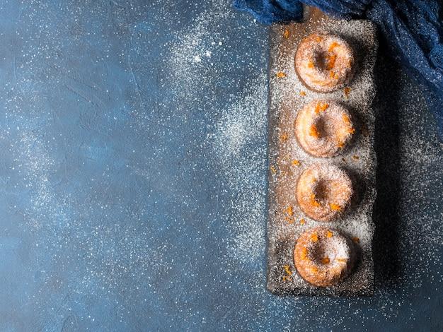 Mini bundt ring cakes met sinaasappelschil poedersuiker op donkerblauw en serveerbord. bovenaanzicht. vakantie kerst zoet eten