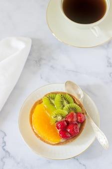Mini cake of taart met custard en diverse soorten fruit in gelei.