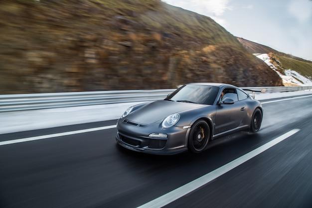 Mini coupe rijden op de snelweg over bergen.