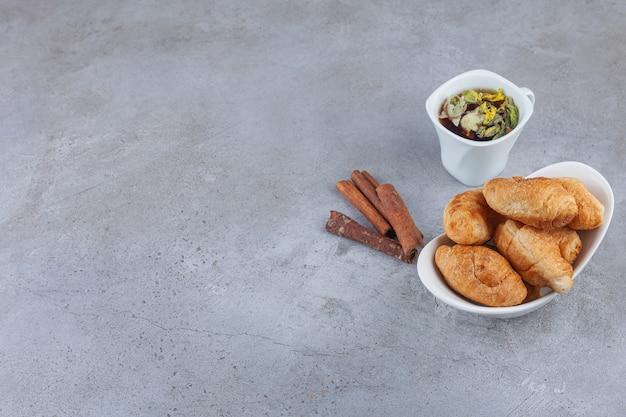 Mini croissants van bladerdeeg met een gouden korst en een kopje thee.