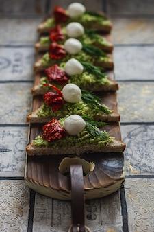 Mini driehoek canapés bruschetta met avocado, mozarella en gedroogde tomaten op het rustieke bord op de vintage betegelde achtergrond.
