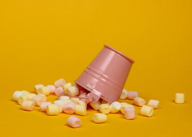 Mini-emmer met veel marshmallows op gele achtergrond. minimalisme. snoepgoed