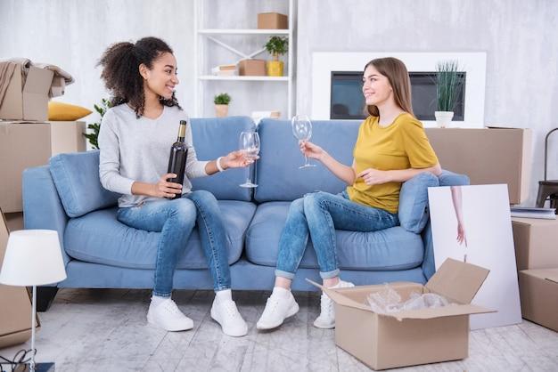 Mini-feest. vrolijke jonge meisjes die op de bank zitten en op het punt staan wat wijn te drinken terwijl ze vieren dat ze naar een nieuw appartement gaan