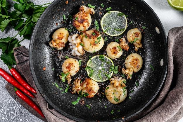 Mini gegrilde inktvis met limoen en kruiden in een pan. grijze achtergrond.