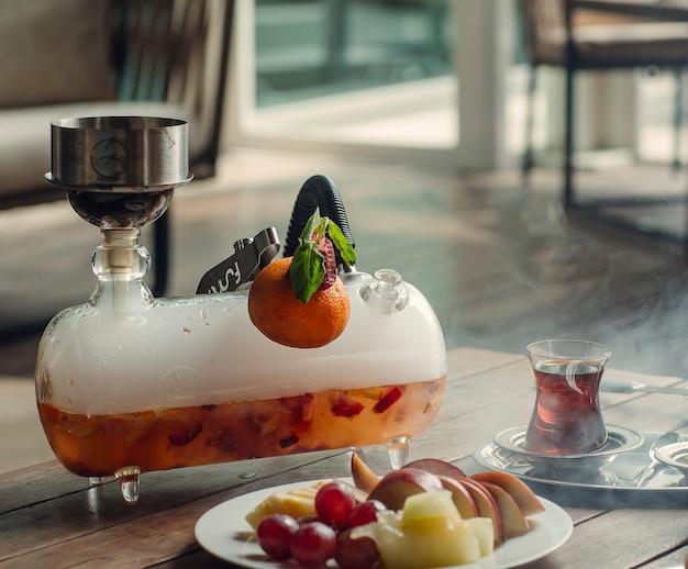 Mini glazen waterpijp shisha met aardbei en sinaasappel smaak bij thee opstelling