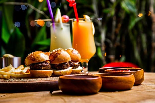 Mini hamburgers frietjes specerijen cocktails zijaanzicht