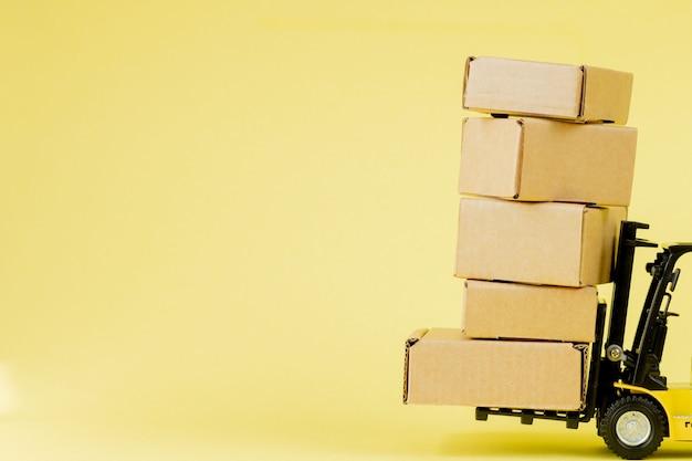 Mini heftruck laden kartonnen dozen. ideeën voor logistiek en transportbeheer en commercieel bedrijfsconcept voor de industrie.