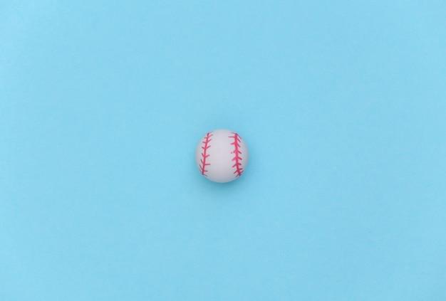 Mini honkbalbal op een blauwe pastel achtergrond. minimalisme sport concept. bovenaanzicht. plat leggen
