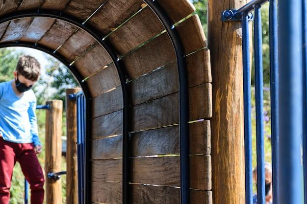 Mini houten tunnel van een parkspeelgoed. in de onscherpe achtergrond, een droevig 8 éénjarigenkind.