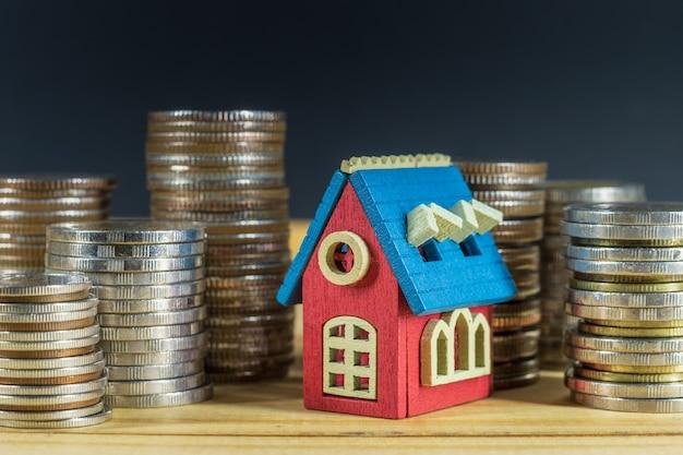 Mini-huis op stapel munten. geld besparen voor vastgoedconcept.