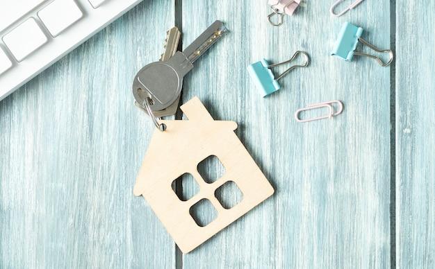 Mini huisbeeldje met sleutels op een roze bureau.