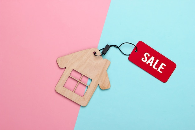 Mini huisfiguur met verkooplabel op roze blauw pastel.