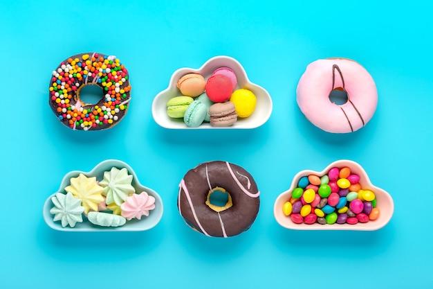 Mini kleurrijke snoepjes in kom in vorm van wolk met geïsoleerde donuts