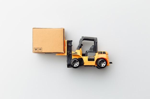 Mini-model van heftruck met kartonnen doos op wit wordt geïsoleerd
