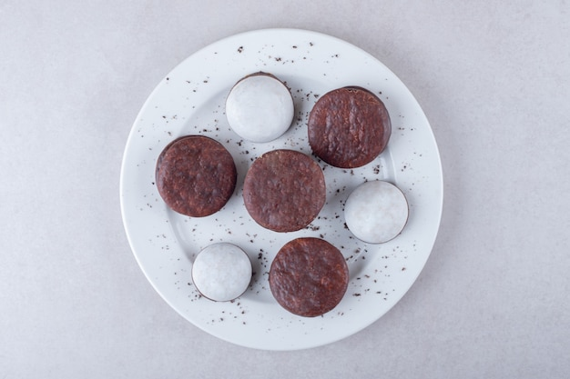 Mini mousse gebak en cholaat gecoat koekjesdessert op een bord, op het marmer.