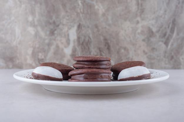 Mini mousse gebak en cholaat gecoat koekjesdessert op een bord op marmeren tafel.