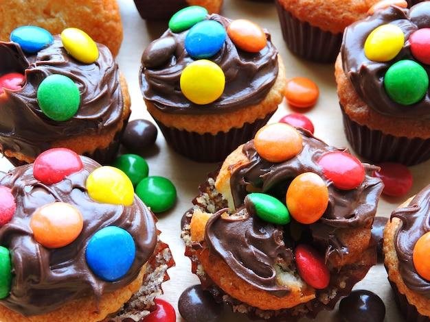 Mini-muffins met topping van chocoladeroom en gekleurd snoep.