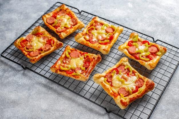 Mini-pizza's van bladerdeeg met worstjes.