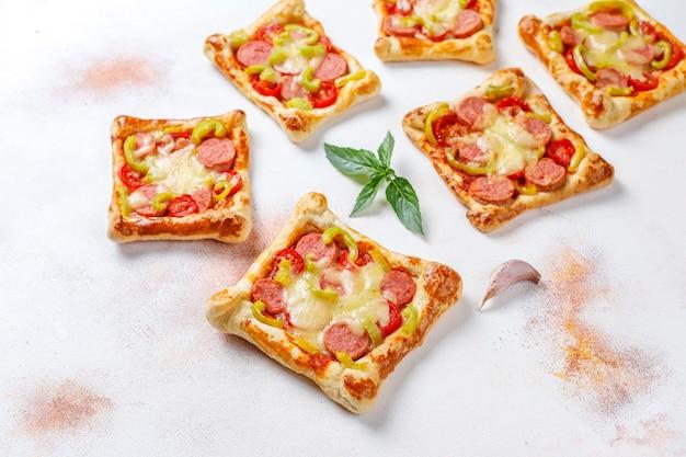 Mini-pizza's van bladerdeeg met worstjes. Gratis Foto