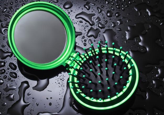 Mini pocket spiegel haarborstel met waterdruppels op een zwarte achtergrond