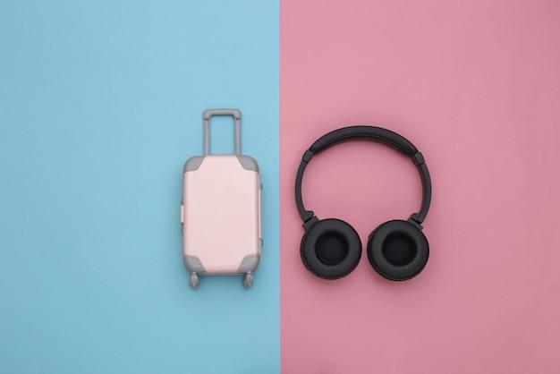 Mini reisbagage en stereo koptelefoon op een blauw-roze pastel achtergrond. klaarmaken voor de reis. bovenaanzicht