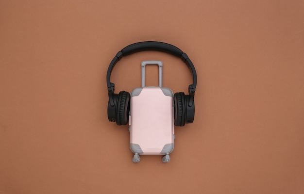 Mini reisbagage met stereo koptelefoon op bruine achtergrond. reisplanning. bovenaanzicht