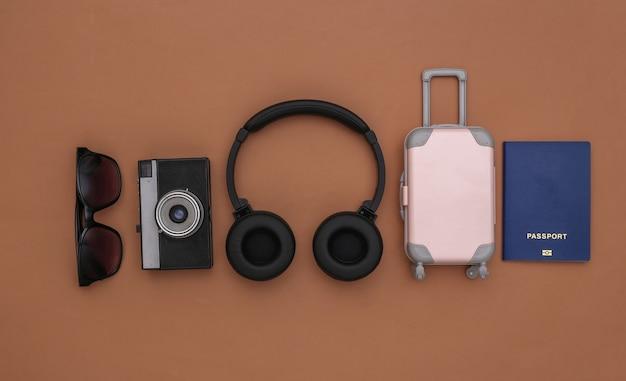 Mini reisbagage met stereo koptelefoon, reisaccessoires op bruine achtergrond. reisplanning. bovenaanzicht