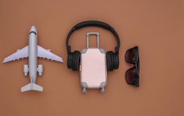 Mini reisbagage met stereo koptelefoon, zonnebril en vliegtuig op bruine achtergrond. reisplanning. bovenaanzicht
