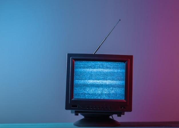 Mini retro tv-antenne-ontvanger. ouderwets tv-toestel. roze blauw gradiënt neonlicht.