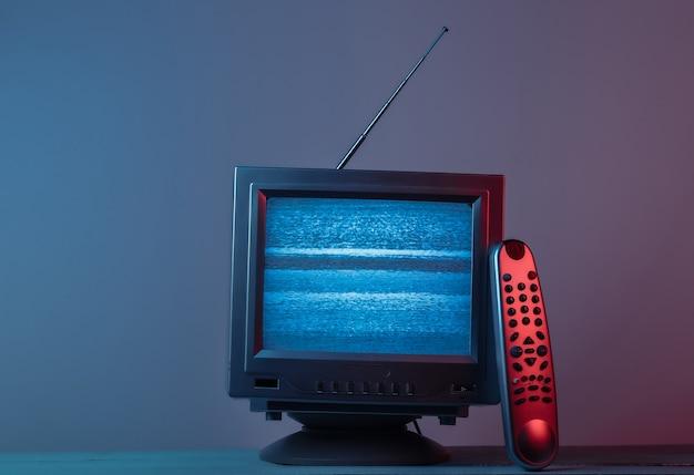 Mini retro tv-antenne-ontvanger. ouderwetse tv met afstandsbediening. rood blauw gradiënt neonlicht
