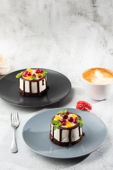 Mini ronde soufflé cake met fruit en chocholate glazuur op topc op marmeren achtergrond. wallpaper voor gebak café of café menu. verticaal.