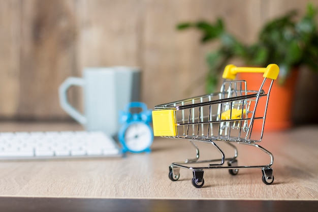 Mini supermarkt trolley op het bureau met toetsenbord, wekker en beker.