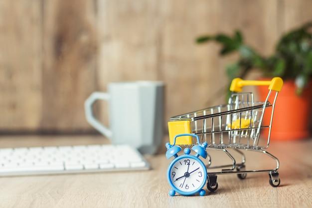 Mini supermarkt trolley, wekker en toetsenbord op het bureau.