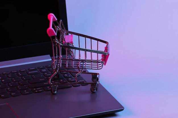 Mini supermarktkarretje op laptop toetsenbord. neon gradiënt rood-blauw, ultraviolet licht. online winkelen