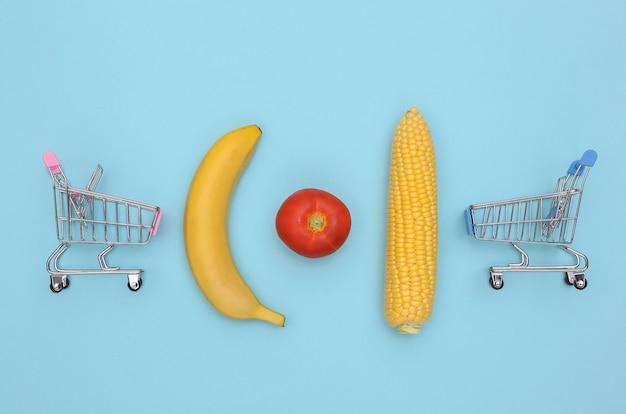Mini supermarktkarretjes, groenten en fruit op blauwe achtergrond.