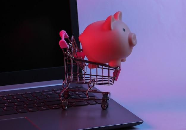 Mini supermarktwagen met spaarvarken op laptop toetsenbord. neon gradiënt rood-blauw, ultraviolet licht. online winkelen