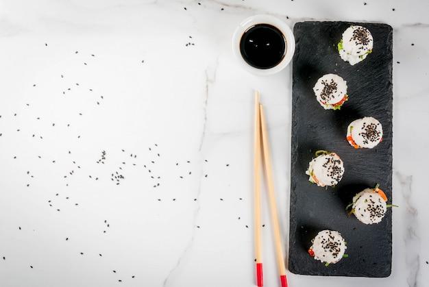 Mini sushi-hamburgers, broodjes met zalm, hayashi wakame, daikon, gember, rode kaviaar.