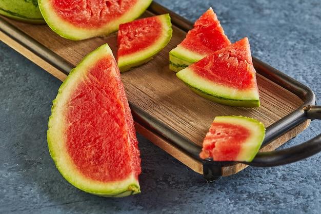 Mini watermeloen met gesneden wiggen op een houten standaard op een blauw.