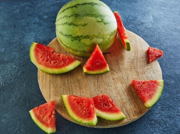 Mini watermeloen met in plakjes gesneden partjes op een ronde houten standaard op een blauw.