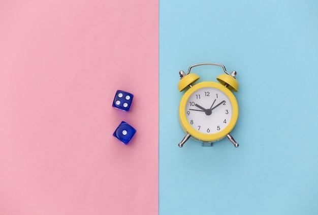 Mini wekker en dobbelstenen op roze blauwe pastel achtergrond.