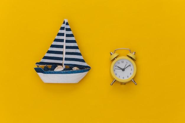 Mini wekker en mini zeilboot op een gele achtergrond. tijd om te reizen.