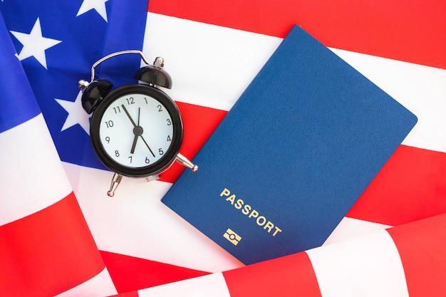 Mini wekker en paspoort op amerikaanse vlag