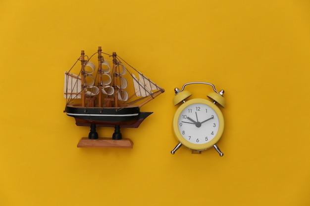 Mini wekker en schip op een gele achtergrond. tijd om te reizen.